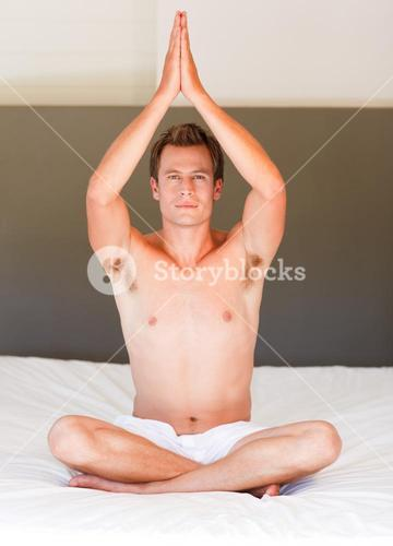 Young boy doing buddha exercises on bed