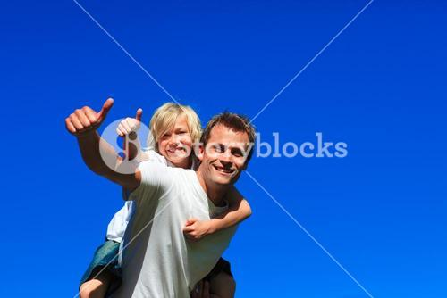 Son on fathers back with thumbs up