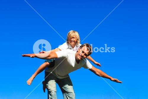 Child on fathers back playing airplane