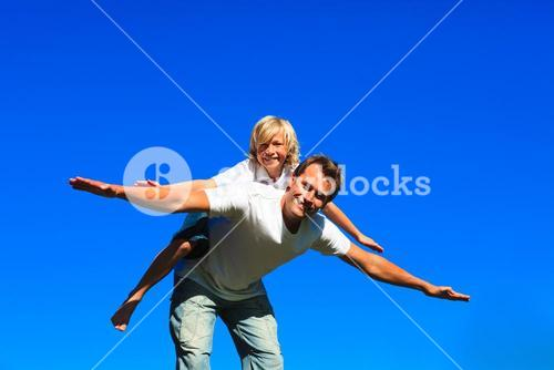 Young boy on fathers back playing airplane