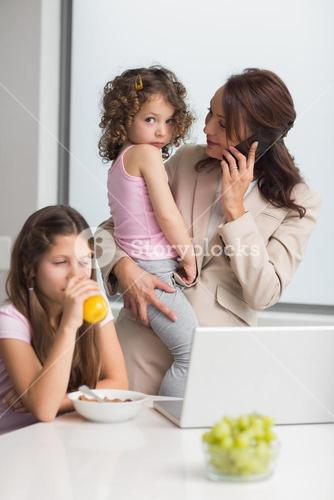 Well dressed mother with daughters and laptop