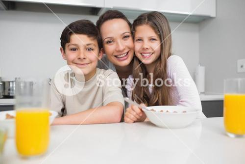 Portrait of a smiling mother with young kids in kitchen