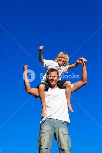 Strong child sitting on his fathers shoulders