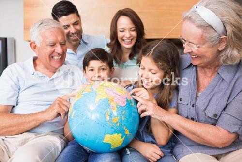 Extended family sitting on sofa with globe in the living room