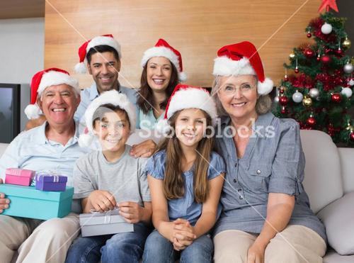 Extended family in Christmas hats with gift boxes in living room