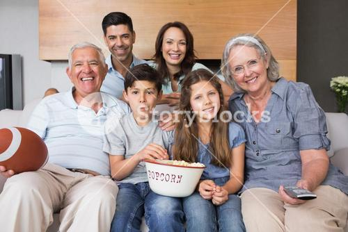 Extended family watching tv on sofa in the living room