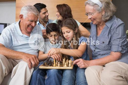 Happy extended family playing chess in the living room