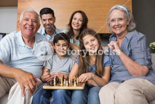 Portrait of happy extended family playing chess in living room