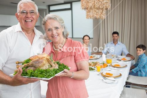 Grandparents holding chicken roast with family at dining table