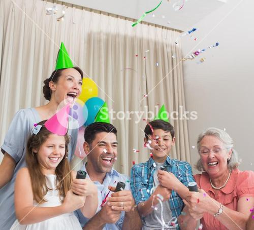 Cheerful extended family playing with Christmas crackers