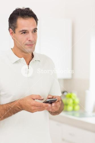 Smiling man text messaging at home