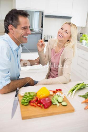 Cheerful couple with chopped vegetables in kitchen
