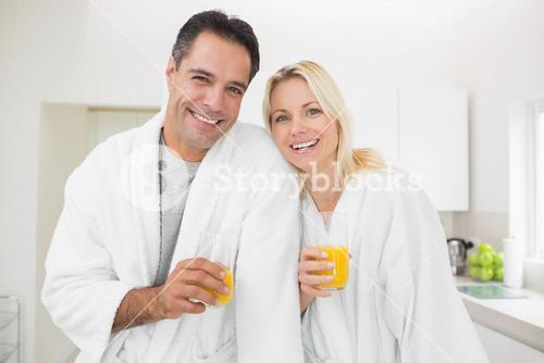 Smiling couple with orange juice glasses in kitchen