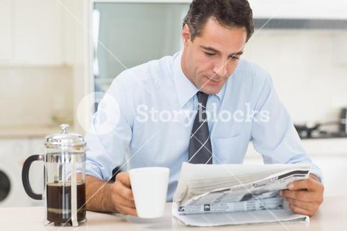 Well dressed man with coffee cup reading newspaper in kitchen