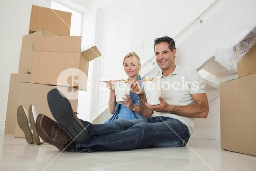 Couple with takeaway food and boxes in a new house