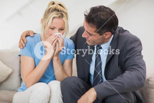 Well dresses man consoling a woman in living room