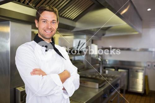 Smiling male cook with arms crossed in kitchen