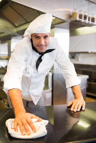 Smiling male cook wiping the counter top in kitchen