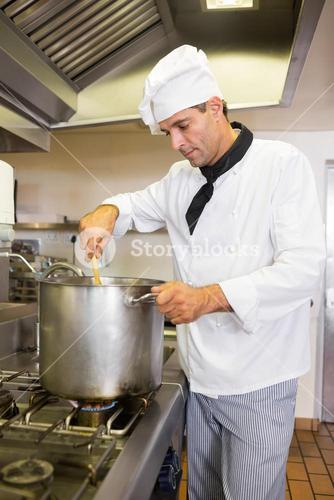 Concentrated male chef preparing food in kitchen