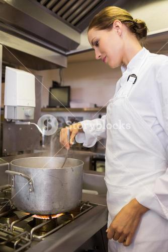 Concentrated female cook preparing food in kitchen