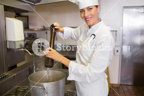 Smiling female cook preparing food in kitchen