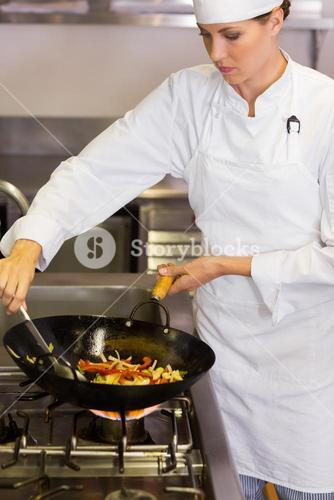Concentrated female chef preparing food