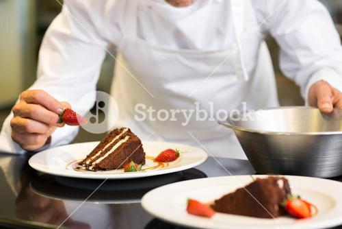 Mid section of pastry chef decorating dessert
