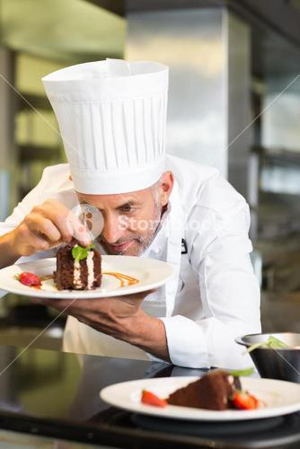 Concentrated male pastry chef decorating dessert in kitchen
