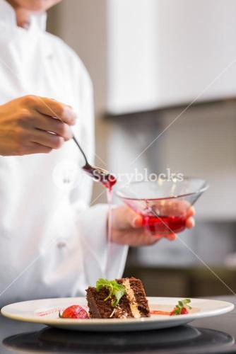 Mid section of a pastry chef decorating dessert in kitchen