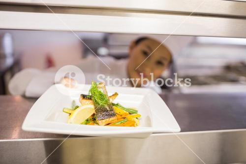 Female chef with cooked food in kitchen