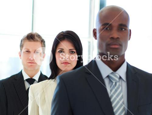Serious businesswoman in focus with her team in a line