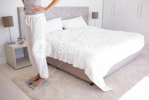 Low section of a woman standing on scale in bedroom