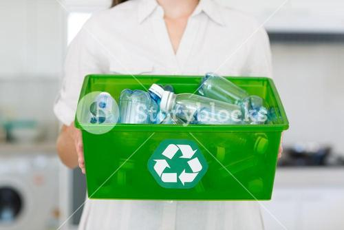 Mid section of woman carrying box with recycling symbol