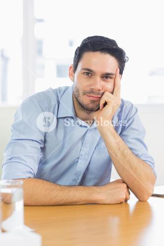Businessman leaning on office desk