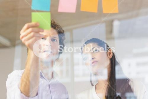 Business people sticking adhesive notes
