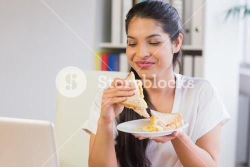Businesswoman eating sandwich in lunch break
