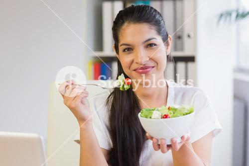 Businesswoman eating salad in office