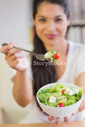 Businesswoman offering salad in office