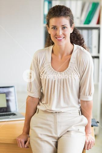 Businesswoman leaning on office desk