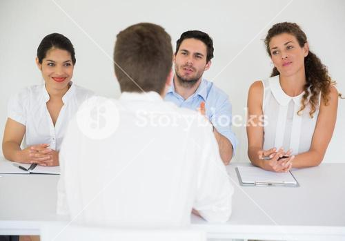 Man being interviewed by business people