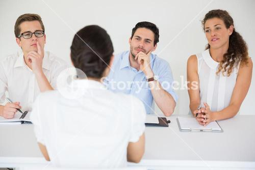 Woman being interviewed by business people