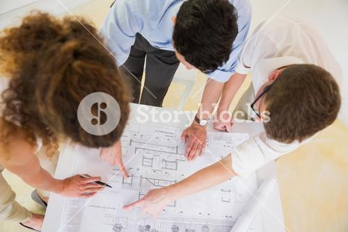 Business people analyzing blueprint