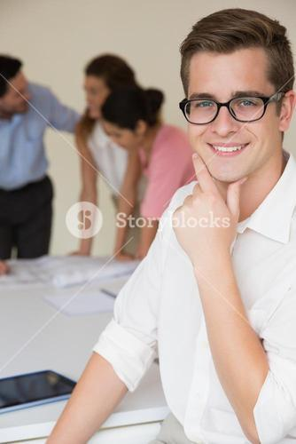 Happy businessman with hand on chin