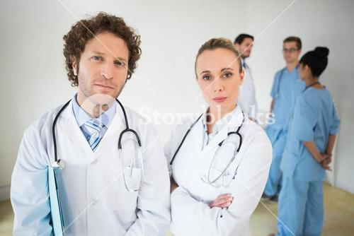 Confident doctors with colleagues in background