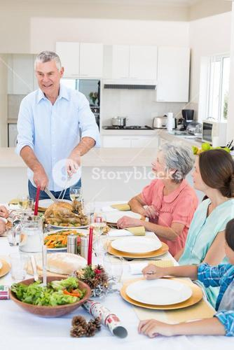Senior man serving meal to family