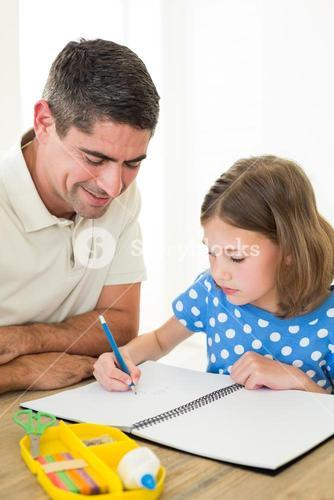 Girl drawing while father sitting by