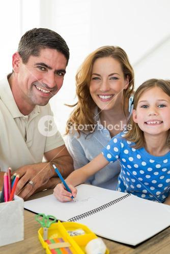 Parents assisting girl in drawing