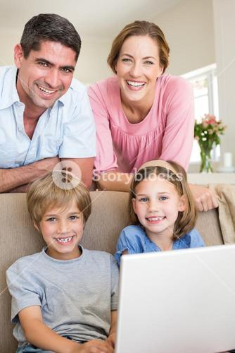 family with laptop in living room