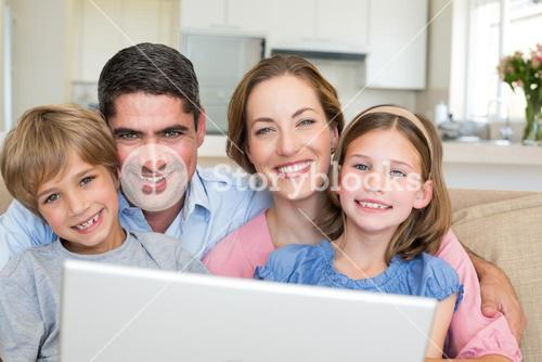 Smiling family with laptop in house