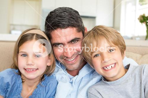 Father and children smiling at home